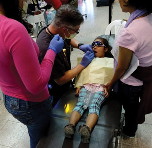 Dentists treating young girl at clinic