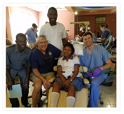 Dr. Brown smiles with his patients at his humanitarian clinic in Haiti
